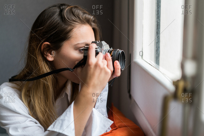 Young pretty photographer aiming with the camera to the window, Horizontal indoors shot,