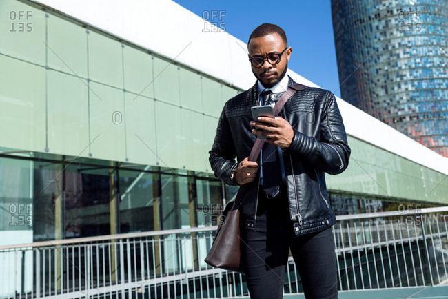 Young stylish man with bag over shoulder standing near building and using phone,