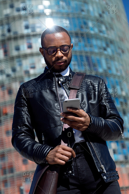 Young trendy gentleman using smart phone on blurred urban background in sun light,