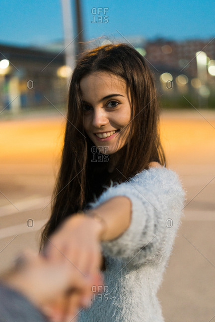 Young woman making a follow me gesture and looking at camera,