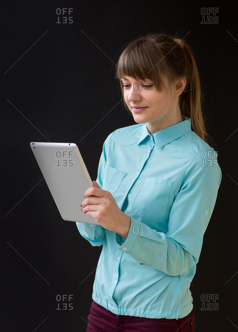 Young woman wearing blue shirt browsing the tablet on the black background, Vertical studio shot,