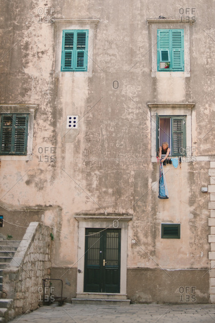 Dubrovnik, Croatia - February 4, 2017: Woman hanging laundry out of her apartment window