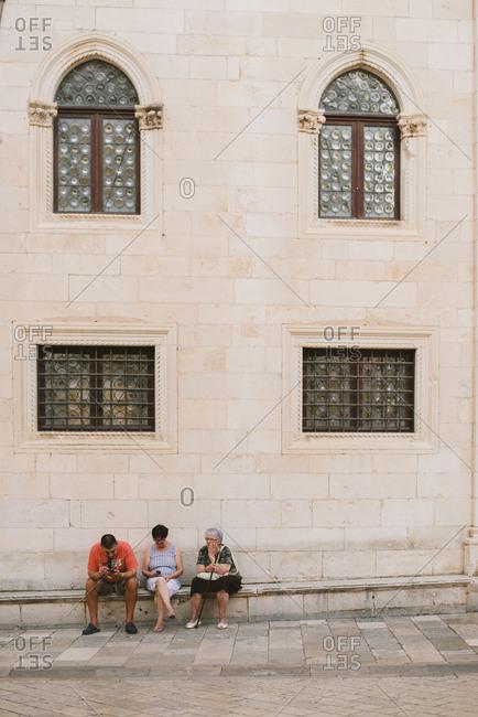 Dubrovnik, Croatia - February 4, 2017: People resting on city bench