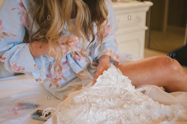 Bride stitching her wedding dress
