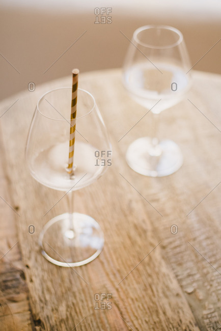 Wine glasses on wooden table with gold straw