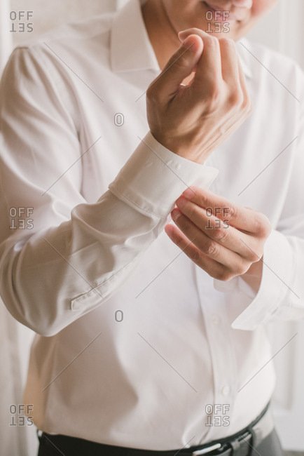 Groom buttoning the sleeve of his shirt