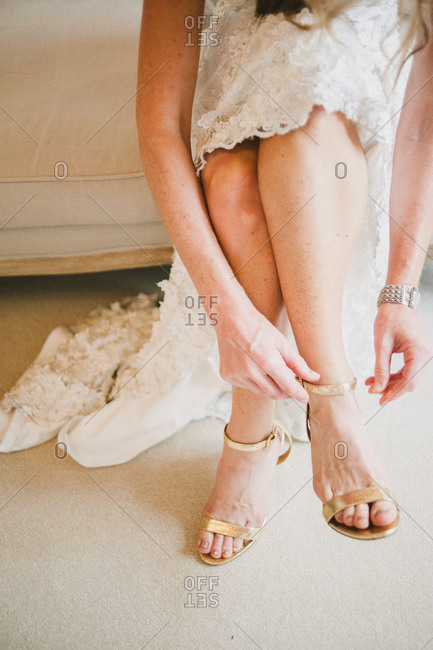 Bride putting gold sandals on
