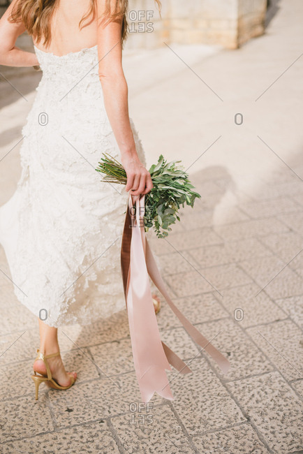 Bride walking with bouquet outdoors