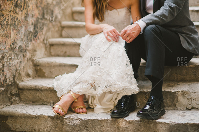 Groom and bride sitting on old cement steps