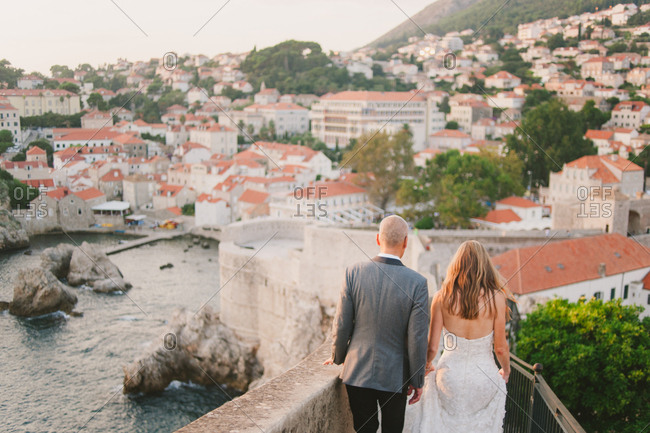 Newlywed couple walking on wall along the coast of Dubrovnik, Croatia