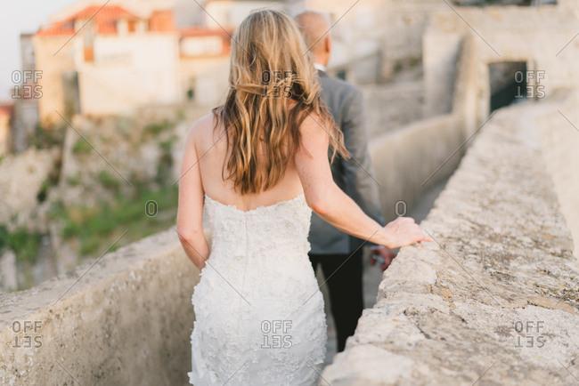 Newlywed couple walking on wall in Dubrovnik, Croatia