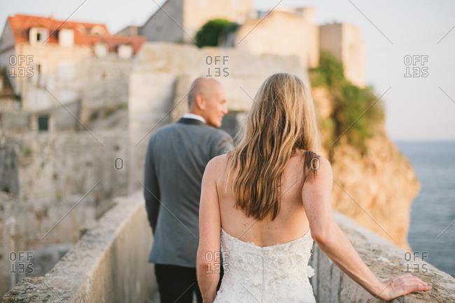 Dubrovnik, Croatia - February 4, 2017: Newlywed couple walking on wall along the coast of Dubrovnik, Croatia