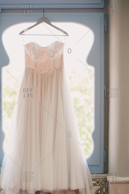 White wedding gown on a wooden hanger in front of a window