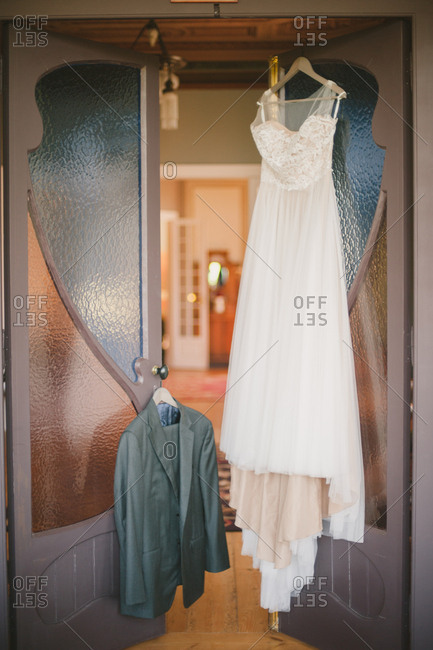 Wedding dress and tux hanging from open doors