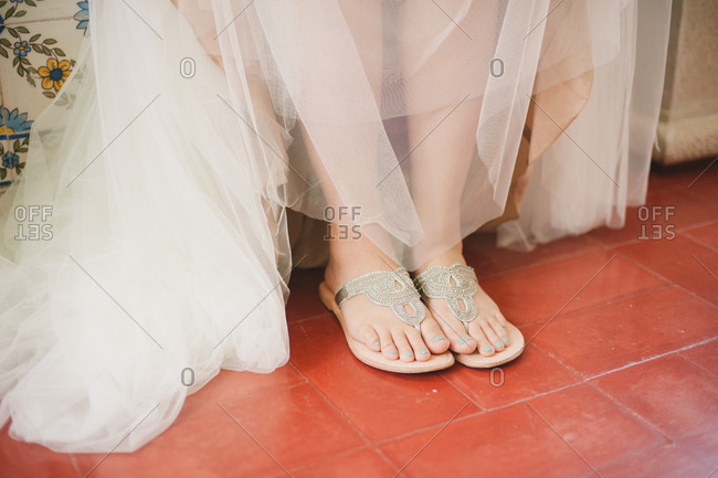 Close up of bride's feet in silver sandals and dress tulle