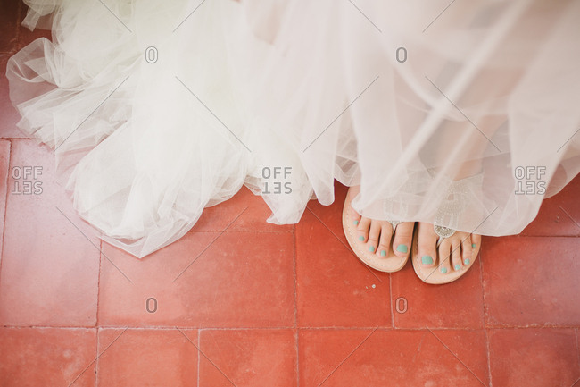 Overhead view of bride's feet in silver sandals and dress tulle