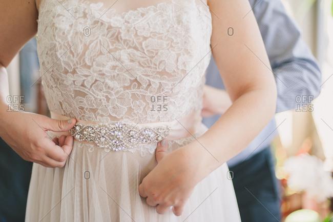 Man tying his bride's belt around her waist
