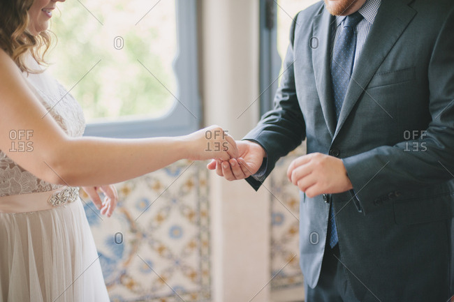 Woman placing object in her groom's hand
