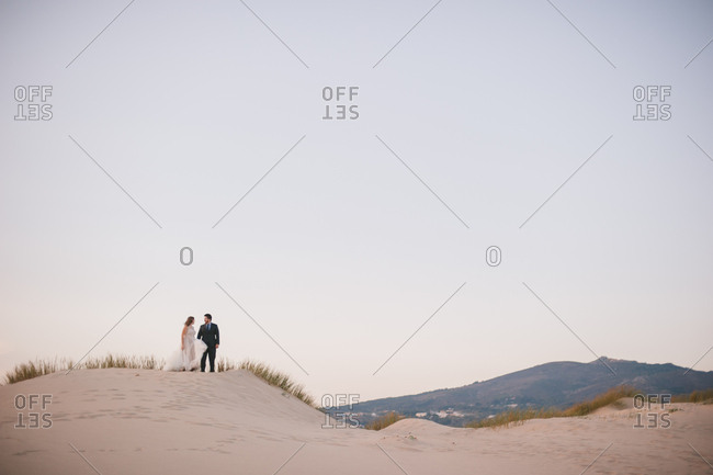 Sintra, Portugal - February 4, 2017: Bride and groom standing on sandy hills in Portugal