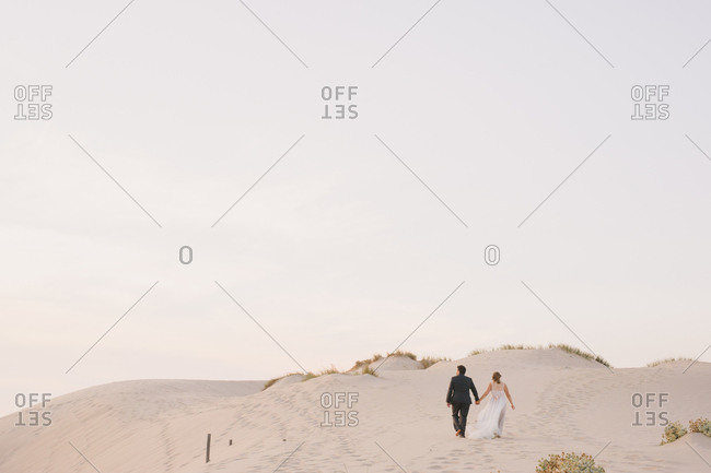 Bride and groom walking hand in hand on sandy hills in Portugal