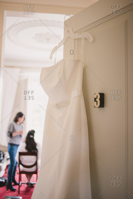 White wedding gown hanging from a door