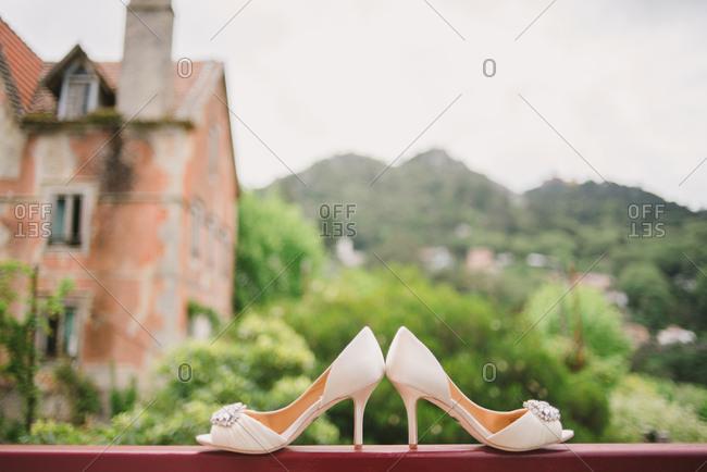 Bride's white heels on railing