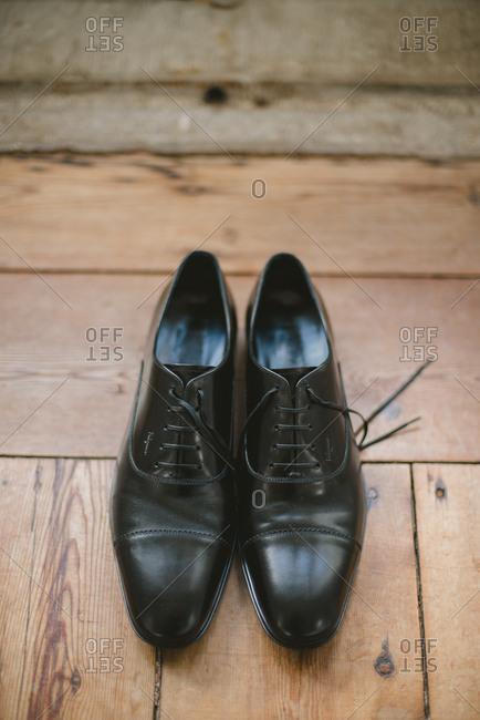 Sintra, Portugal - February 4, 2017: Groom's black shoes on hardwood floor