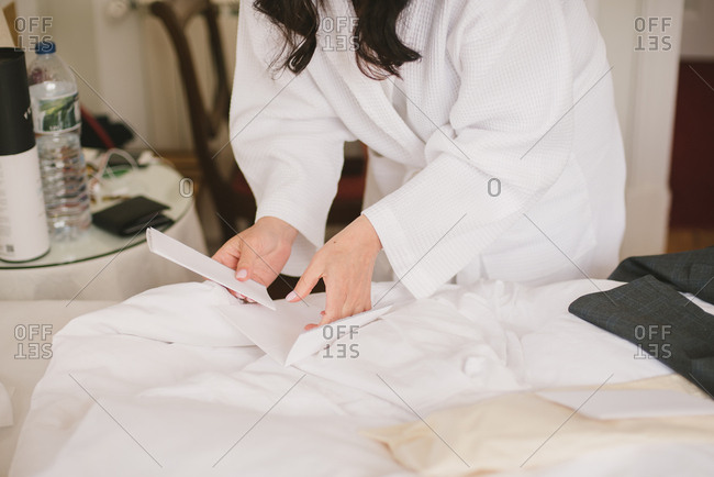 Bride in white robe holding a note