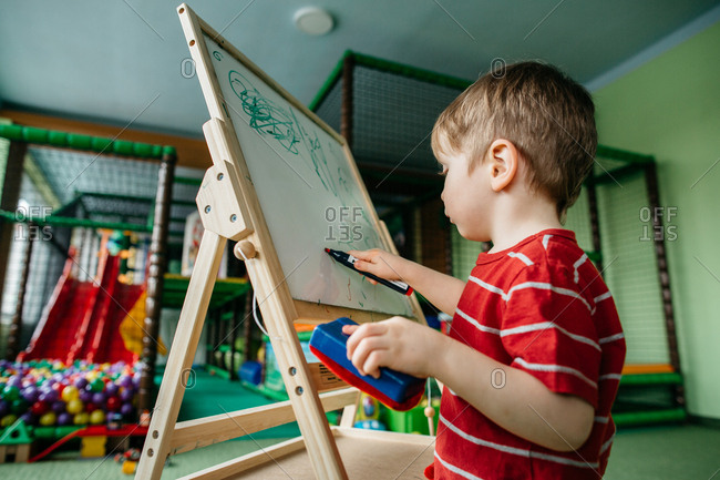 Little boy writing on a drawing board at a play center
