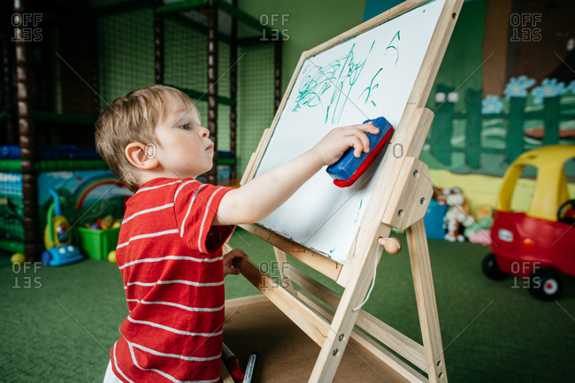 Little boy scribbling on a drawing board at a play center