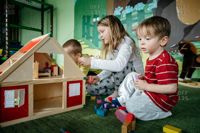Children playing with a wooden doll house and peg people in a play center