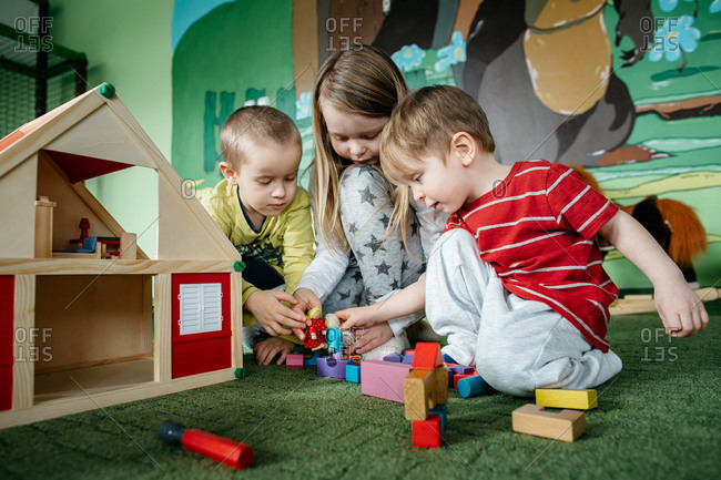 Busy children playing with a wooden doll house and peg people in a play center