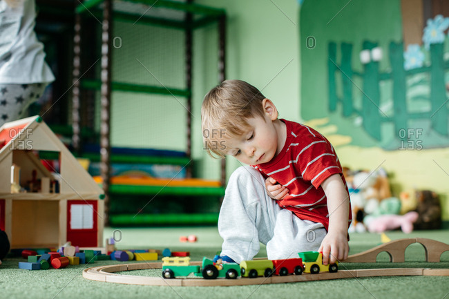 Little boy playing with a wooden train in an indoor playground