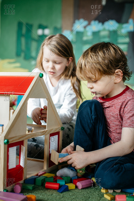 Siblings playing together with a doll house and peg people