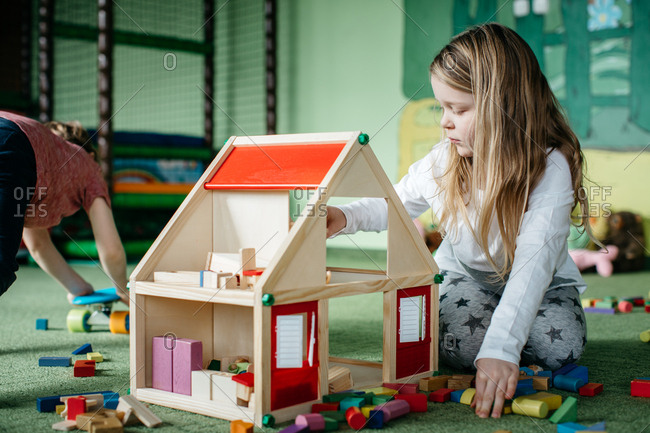 Young girl playing with a wooden doll house in an indoor playground