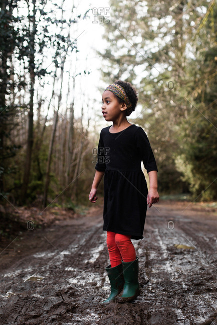 Girl playing in mud on a country road