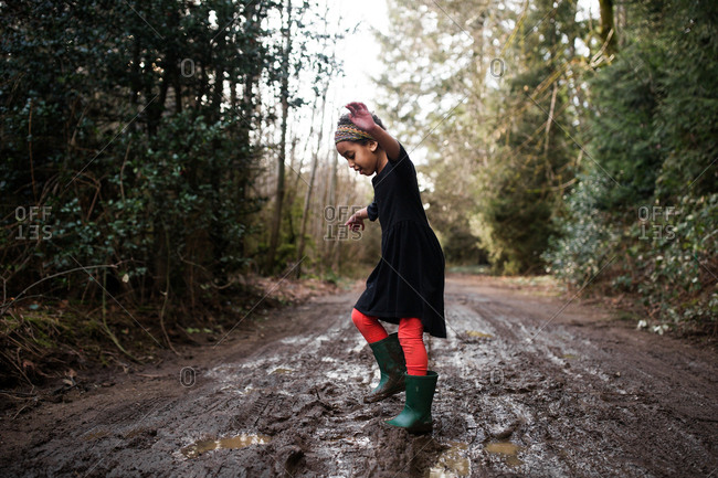Young girl stomping in mud on a country road