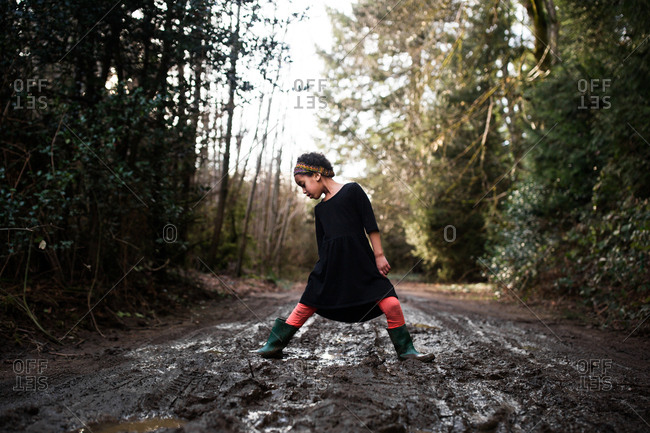 Girl standing in mud on a country road