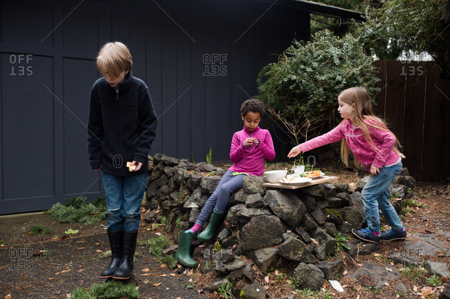 Three kids having snack outdoors
