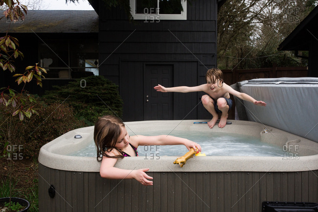 Siblings playing in a hot tub
