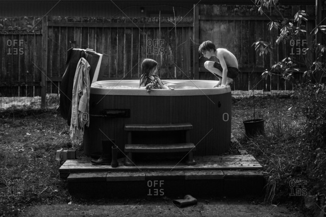 Two kids in a hot tub in black and white