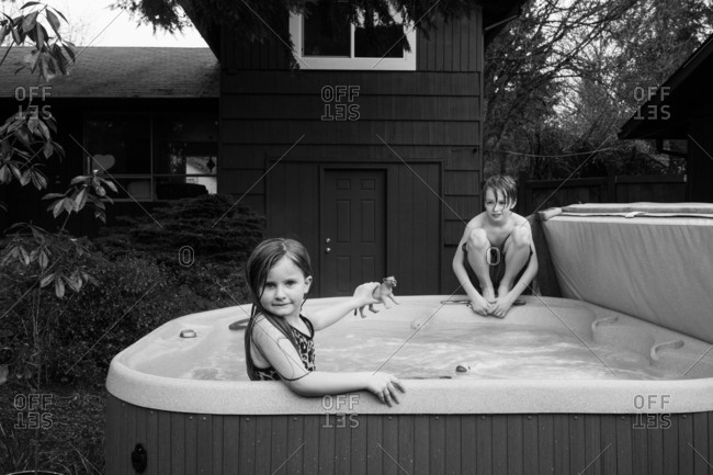 Two kids playing in a hot tub in black and white