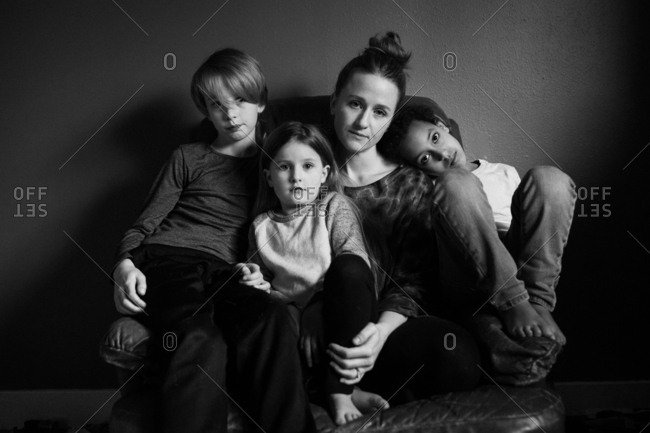 Family sitting together on a recliner in black and white