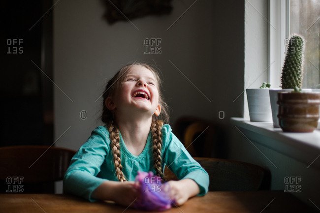 Little girl sitting at table laughing