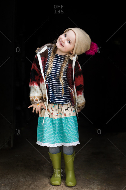 Happy little girl wearing rubber boots and knit hat