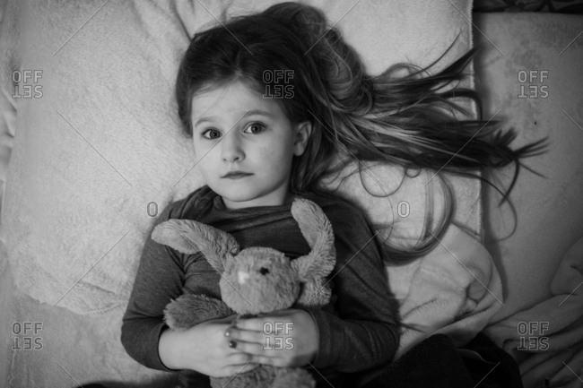 Little girl lying in bed with stuffed animal