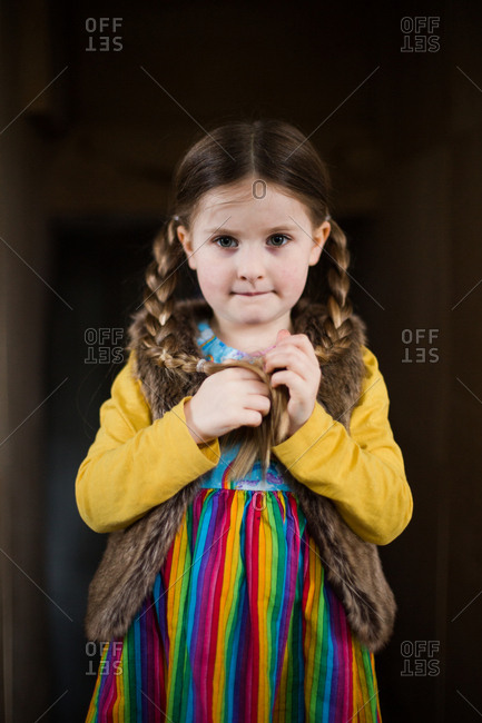 Portrait of a little girl with braids and a colorful outfit