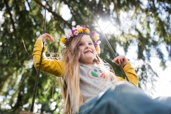 High angle view of a little girl wearing floral crown on a swing