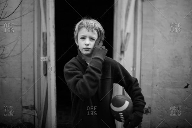 Boy holding football in black and white