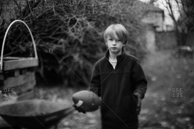 Boy playing with football in black and white